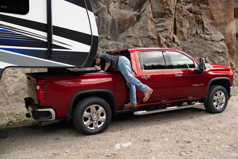 A man uses the exterior side step of the 2020 Chevy All-New Silverado HD Truck for an easier reach to bed  storage