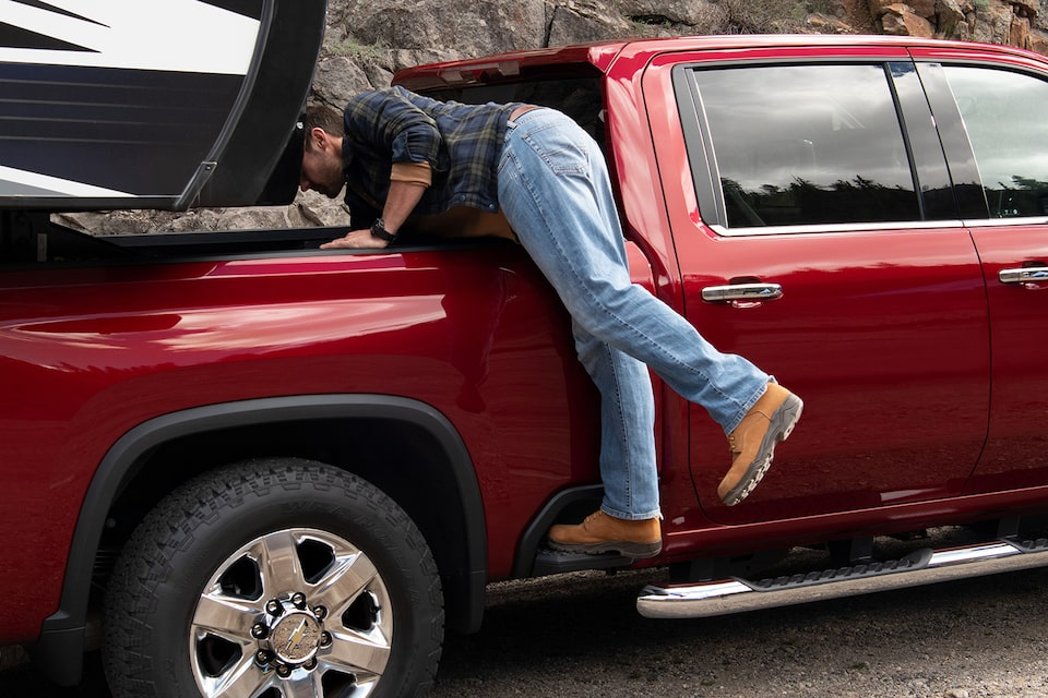 A man uses the exterior side step of the 2021 Chevy Silverado HD Truck for an easier reach to bed  storage