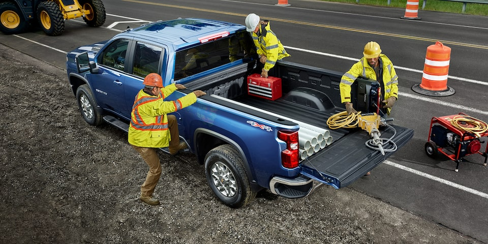 Two men using the 2021 Chevy Silverado HD Truck bed for commercial work
