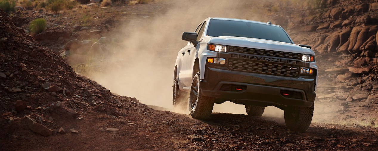 A white 2021 Chevy Silverado 1500 driving through the dirt with a diesel engine