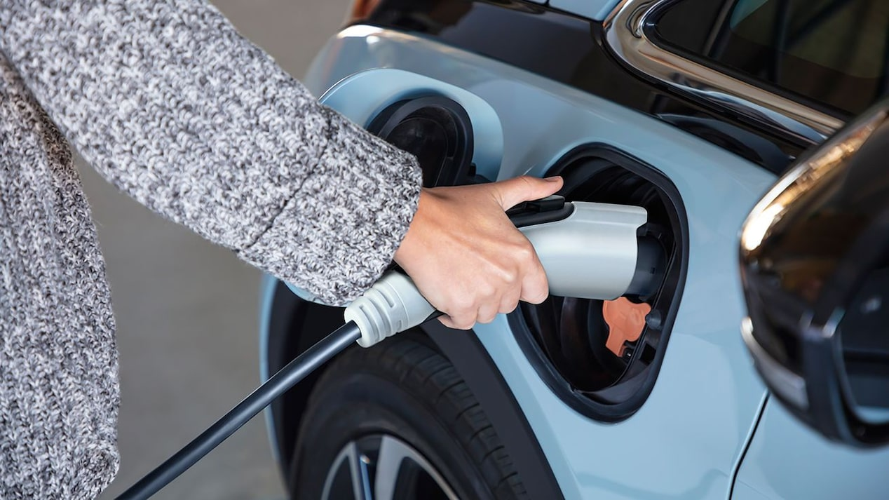 A person charging a blue 2022 Chevy Bolt electric vehicle